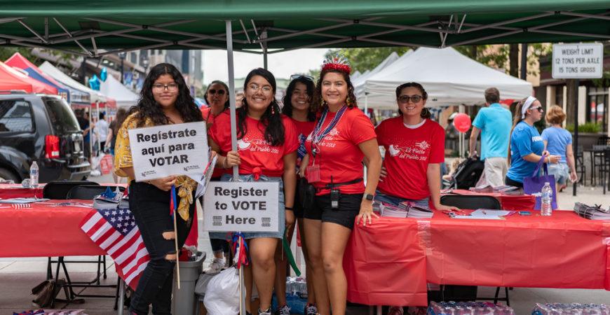 Iliana Santillán, Maria Gonzalez, and volunteers registering voters at their booth during La Fiesta del Pueblo 2018