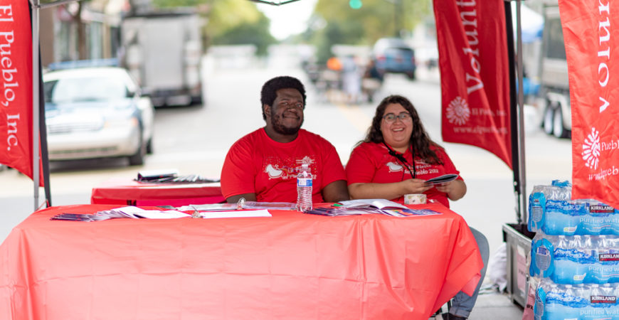 Mary José Espinosa and Tavon Bridges at a booth during La Fiesta del Pueblo.