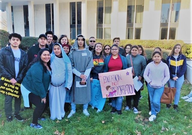 Picture of our youth and other volunteers at the No Room at the Inn action in December 2018. Una foto de nuestros jóvenes durante una acción antes de la Navidad 2018.