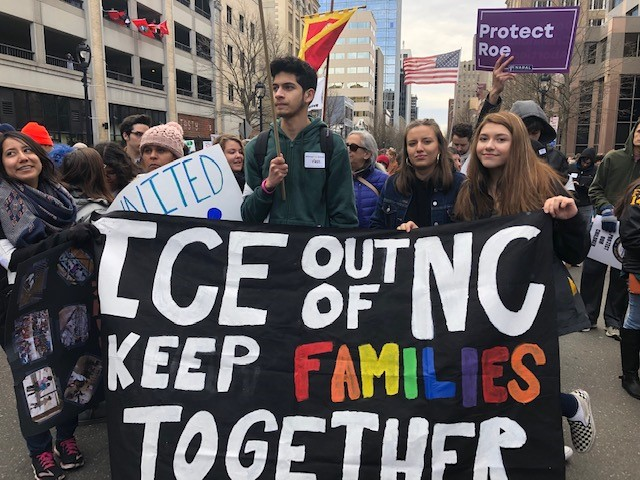 """HKonJ March, youth holding a """"ICE out of NC Keep Families Together"""" Banner"""